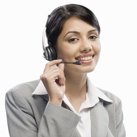 Female customer care executive wearing a headset against a white background 版權商用圖片