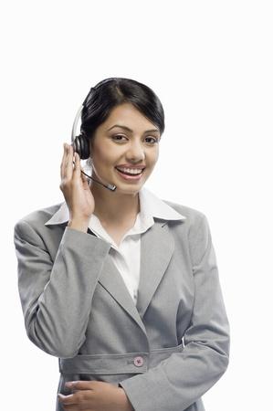 Female customer care executive wearing a headset against a white background 版權商用圖片