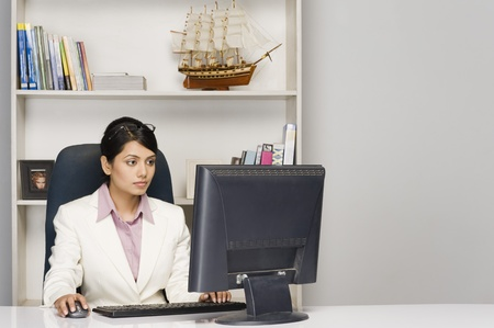 Businesswoman working on a desktop PC in an office Stock Photo - 10126233