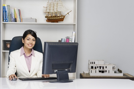 corporate culture: Portrait of a businesswoman working on a desktop PC in an office