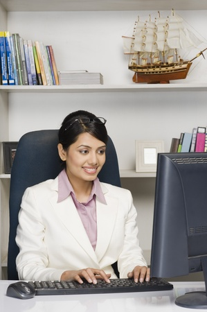 Businesswoman working on a desktop PC in an office Stock Photo - 10123646