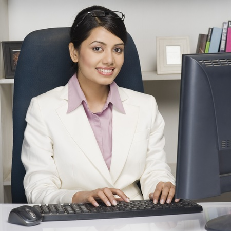 working at office: Portrait of a businesswoman working on a desktop PC in an office