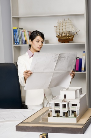 home office: Businesswoman looking at a blueprint in an office