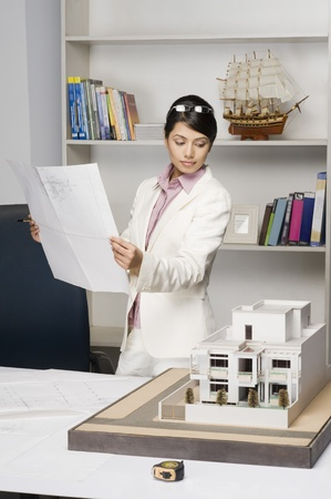 Businesswoman holding a blueprint and looking at a model home in an office Stock Photo