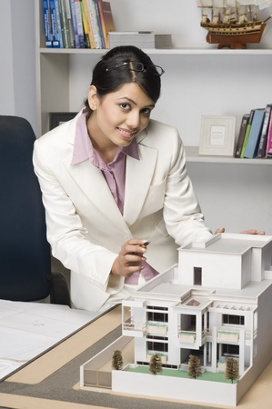 Portrait of a businesswoman near a model home in an office Stock Photo - 10123654