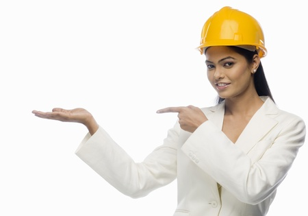 Portrait of a female architect pointing towards her palm Imagens