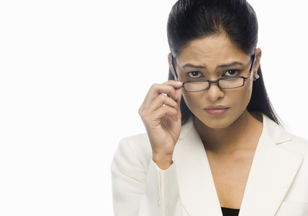 photosindia: Portrait of a curious businesswoman holding her eyeglasses LANG_EVOIMAGES
