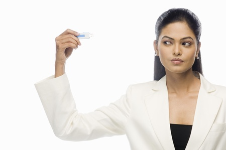 Businesswoman looking at a flash drive LANG_EVOIMAGES