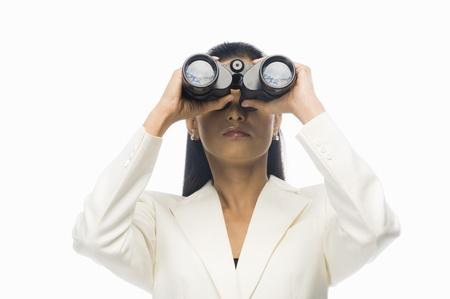 observation: Businesswoman looking through binoculars