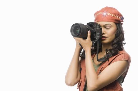 photosindia: Female photographer photographing with digital camera