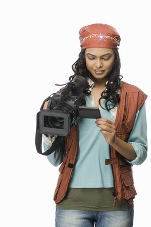 photosindia: Female videographer looking at video camera