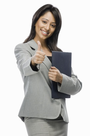 Portrait of a businesswoman holding files and showing thumbs up