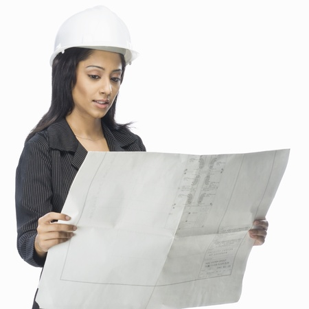architect: Female architect looking at a blueprint LANG_EVOIMAGES