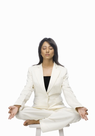 Businesswoman meditating on a stool