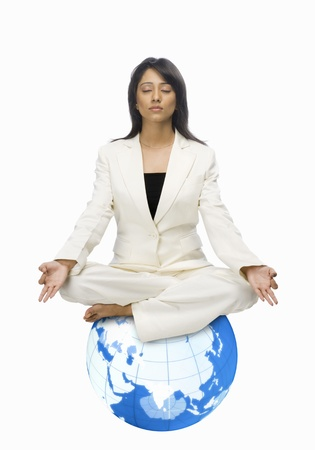 Businesswoman meditating on a globe Stock Photo - 10126329