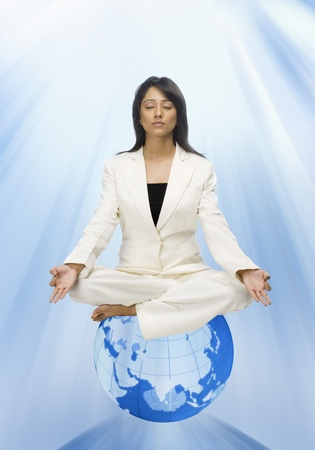 Businesswoman meditating on a globe