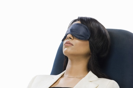 asleep chair: Businesswoman wearing eye mask and sleeping LANG_EVOIMAGES
