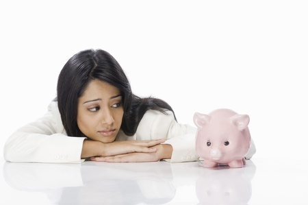 Businesswoman looking at a piggy bank Stock Photo - 10123502