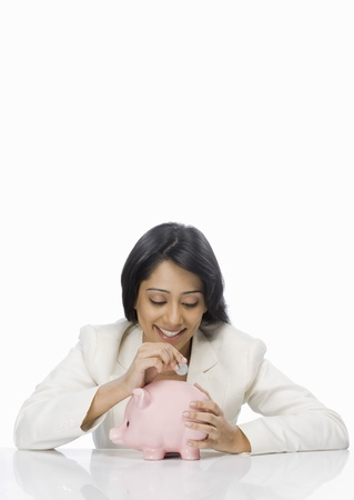 Businesswoman inserting a coin into a piggy bank Archivio Fotografico