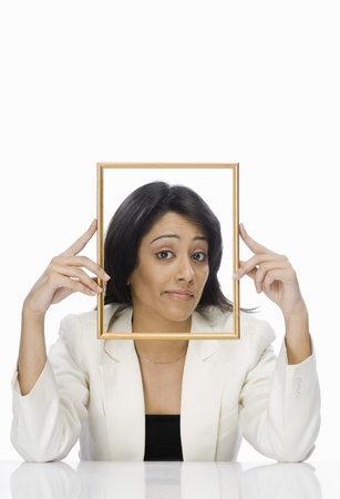 Businesswoman looking through a picture frame Stock Photo - 10123540