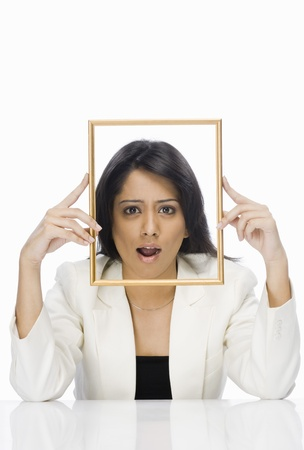 Businesswoman looking through a picture frame Stock Photo - 10123557