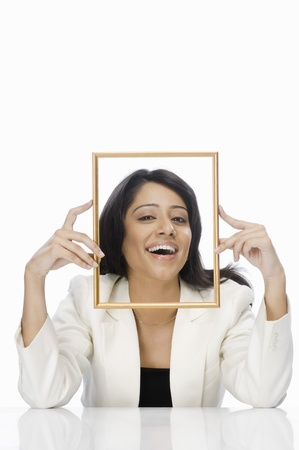 Businesswoman looking through a picture frame Stock Photo - 10126259