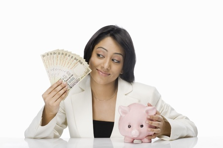 budgeting: Businesswoman holding Indian paper currency and piggy bank