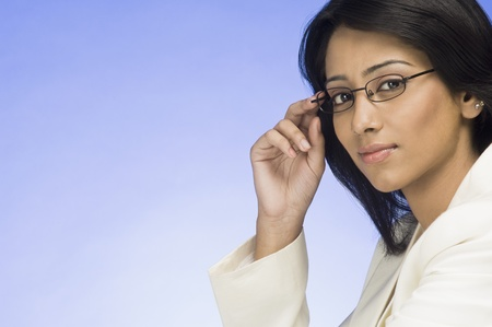 Portrait of a businesswoman holding her eyeglasses Stock Photo - 10123643
