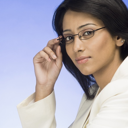 Portrait of a businesswoman holding her eyeglasses Stock Photo