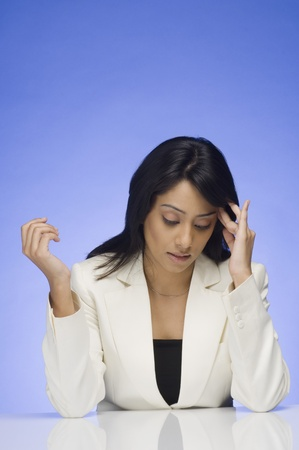 wearying: Frustrated businesswoman rubbing her temple