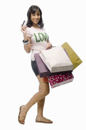 Young woman carrying shopping bags and a credit card Stock Photo - 10126308