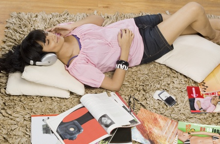 Young woman listening music in a living room Stock Photo - 10125959