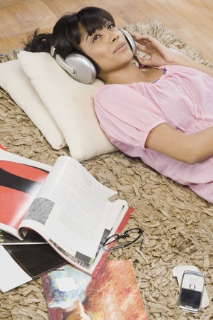 listening back: Young woman listening music in a living room LANG_EVOIMAGES
