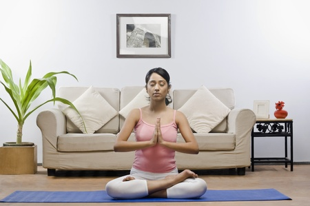 self conscious: Young woman meditating in a living room