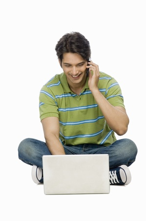 Young man using a laptop and talking on a mobile phone Stock Photo - 10126173