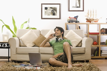 Young man talking on a mobile phone in the living room 版權商用圖片