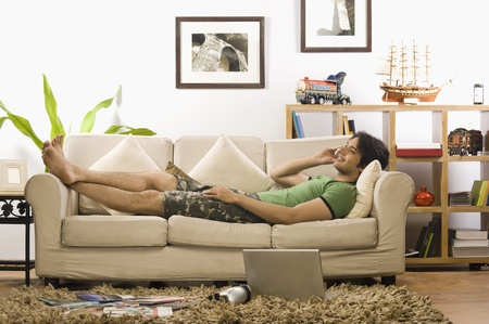 lying on couch: Young man talking on a mobile phone in the living room LANG_EVOIMAGES