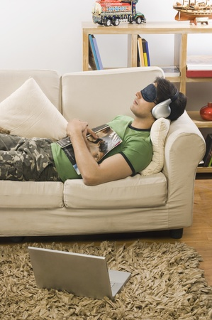 Young man lying on a couch and listening to music 스톡 콘텐츠