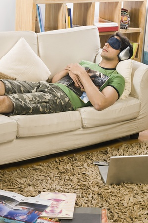 eye pad: Young man lying on a couch and listening to music LANG_EVOIMAGES
