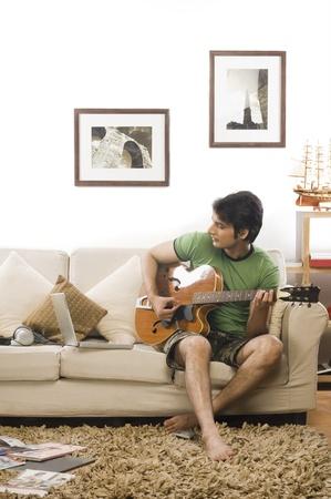 リビング ルームでギターを演奏若い男