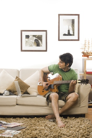 man playing guitar: Young man playing a guitar in the living room