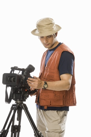 Young male videographer adjusting a videography camera on a tripod Stock Photo - 10126230