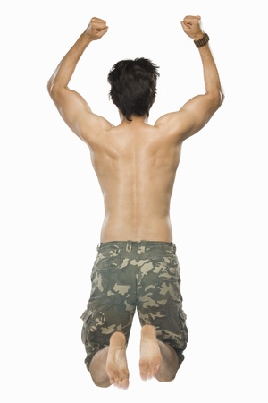 Rear view of a young man jumping with joy Stock Photo - 10126294