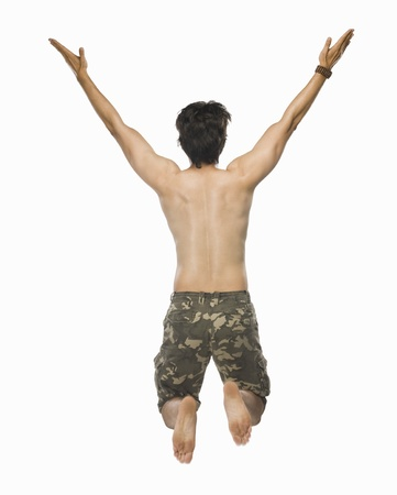 Rear view of a young man jumping with joy