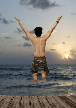 freedom leisure activity: Rear view of a young man jumping with joy over a pier