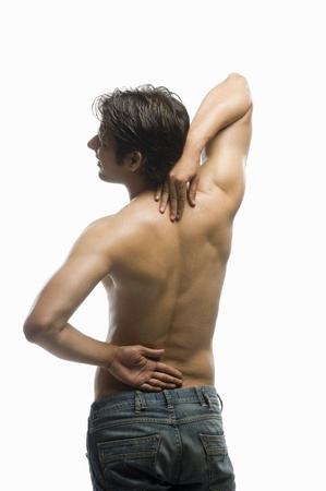 back strain: Rear view of a young man suffering from backache LANG_EVOIMAGES