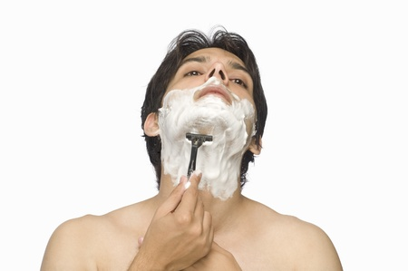 Young man shaving his face Stock Photo - 10123542
