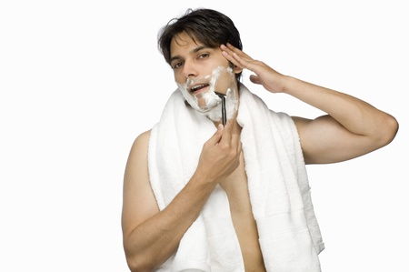 Young man shaving his face