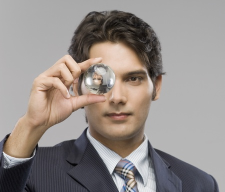 Close-up of a businessman looking at a crystal ball Stock Photo