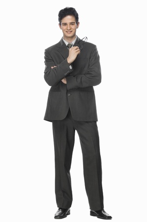 photosindia: Portrait of a businessman holding his eyeglasses